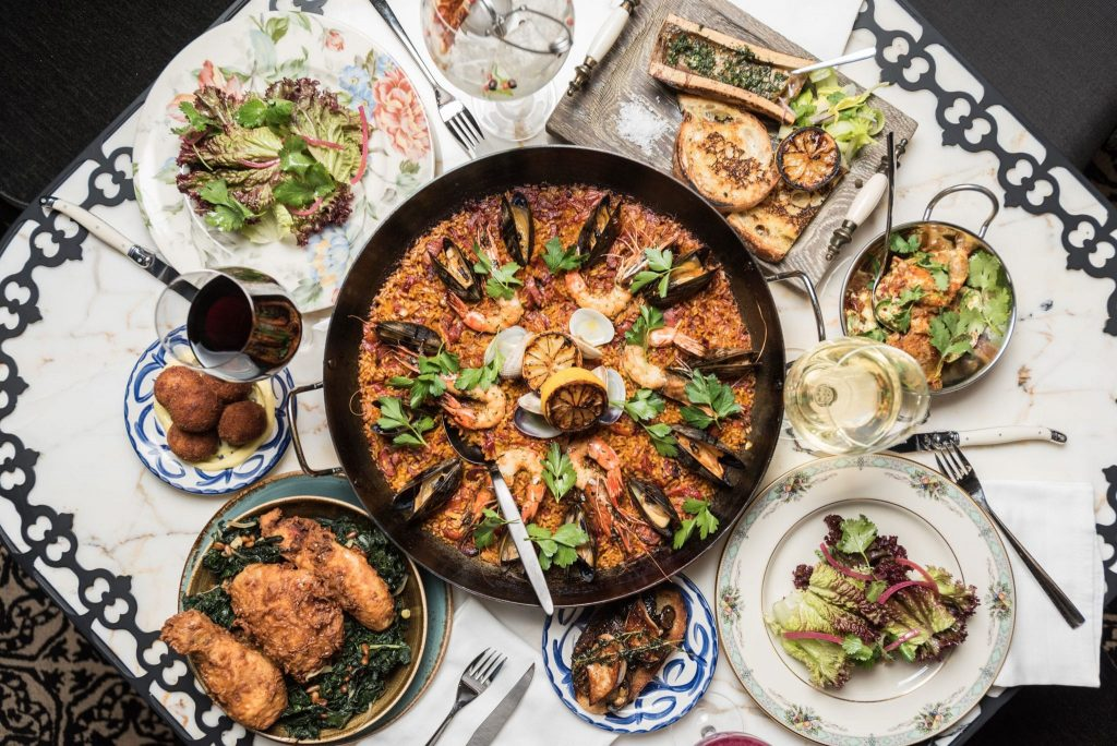 overhead shot of paella dish in the center and smaller side dishes surrounding it