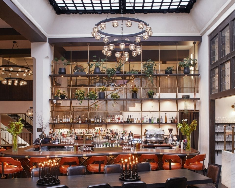 bar with high ceiling and large rectangular table with chairs