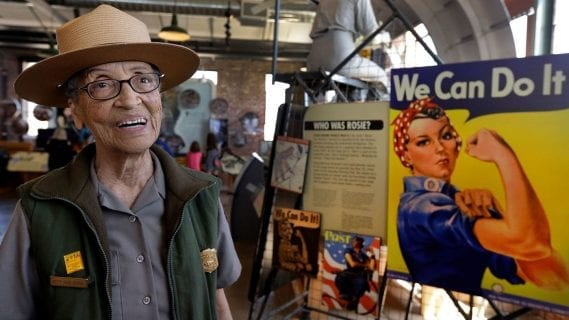 older woman smiling wearing forest ranger uniform next to rosie the riveter poster