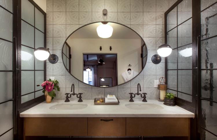 bathroom with dual sinks and large mirror