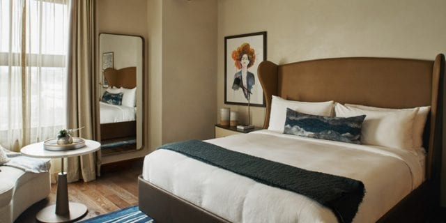room with king bed, chair and small table