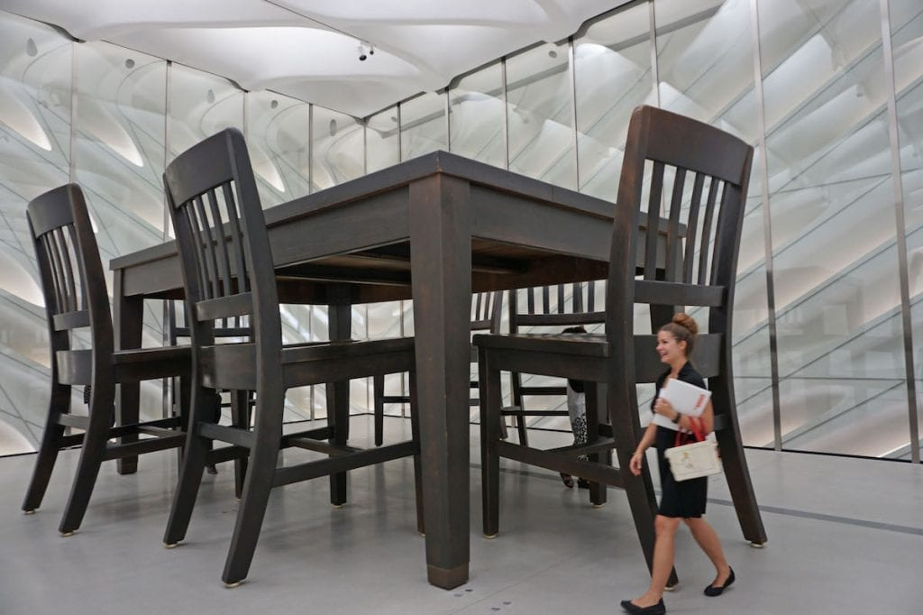 woman walking past giant dining table and chair