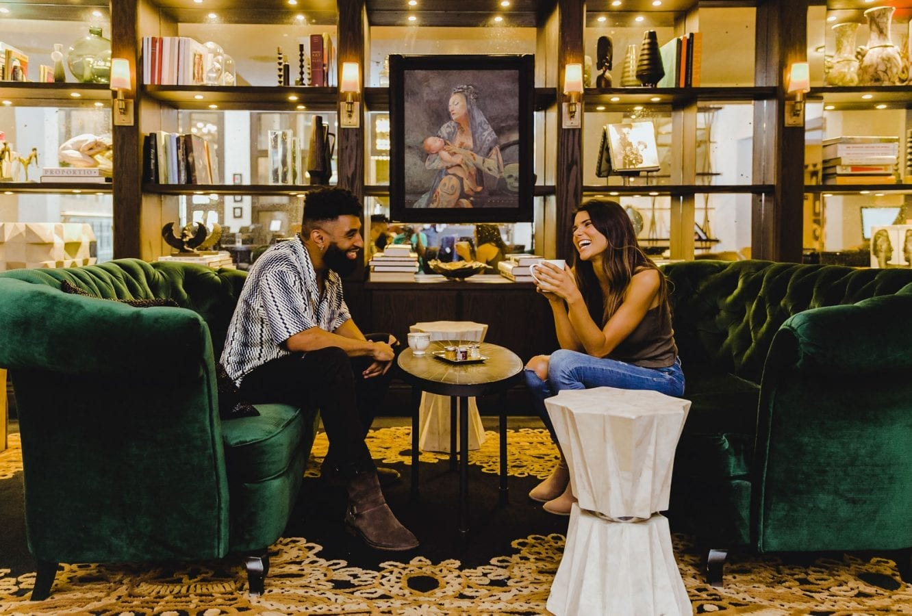 man and woman sitting on plush chairs having coffee and smiling